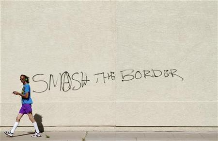 "A man walks past graffiti on a building reading ""Smash The Border"" in Phoenix"